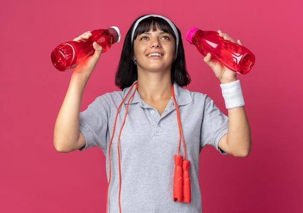 Giovane ragazza fitness che indossa fascia con corda per saltare intorno al collo che tiene due bottiglie d'acqua felice e allegra in piedi su sfondo rosa