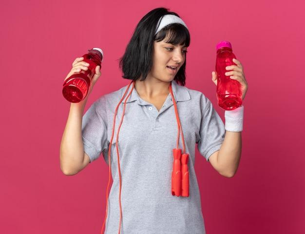 Giovane ragazza fitness che indossa fascia con corda per saltare intorno al collo tenendo due bottiglie d'acqua che sembrano confuse avendo dubbi