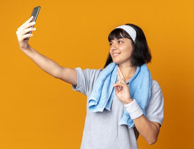 머리띠를 하고 목에 수건을 두른 젊은 피트니스 소녀는 주황색 배경 위에 서 있는 v-sign을 보여주는 스마트폰 미소를 사용하여 셀카를 하고 있습니다.