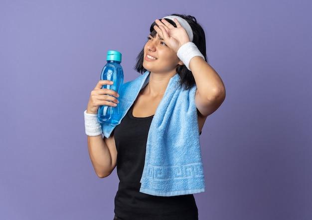 Giovane ragazza di forma fisica che indossa la fascia con l'asciugamano intorno al collo che tiene la bottiglia d'acqua che sembra stanca e oberata di lavoro in piedi su sfondo blu