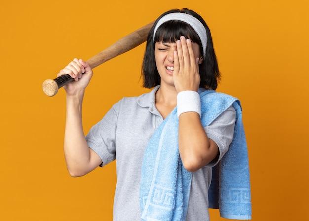 오렌지 위에 서있는 손으로 눈을 덮고 혼란스럽고 불쾌한 야구 방망이를 들고 그녀의 어깨에 수건으로 머리띠를 착용하는 젊은 피트니스 소녀