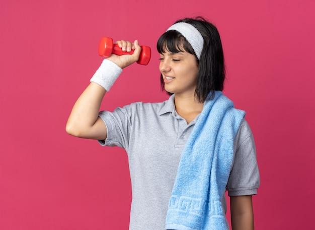머리띠를 하고 어깨에 수건을 두르고 아령을 들고 분홍색 배경 위에 서서 불쾌해 보이는 운동을 하는 젊은 피트니스 소녀