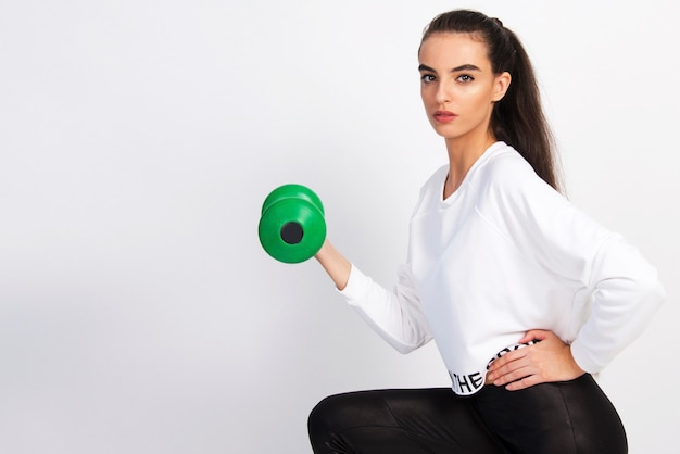 Young fitness girl with exercise weight on white background