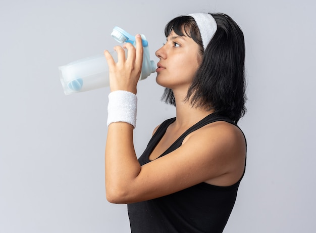 Young fitness girl with headband and armbands drinking water from bottle standing over white