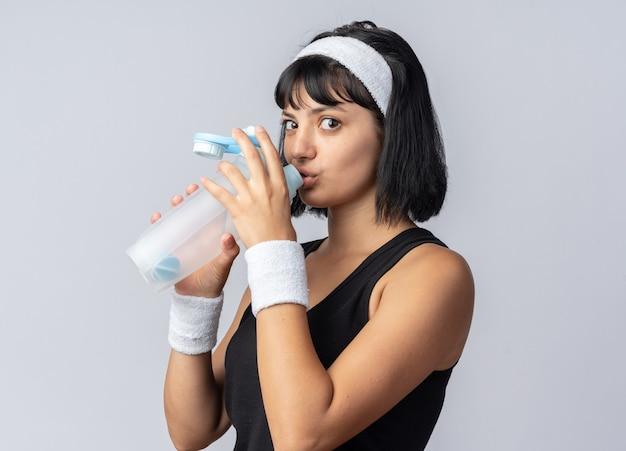 Giovane ragazza fitness con fascia e bracciali che bevono acqua dalla bottiglia in piedi sopra il bianco