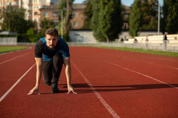 スタジアムで走る準備ができている若いフィットネス男。テキスト用のスペース