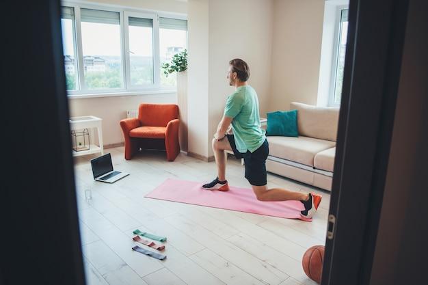 Молодой фитнес-инструктор, имеющий онлайн-уроки фитнеса, растягивается, используя ноутбук