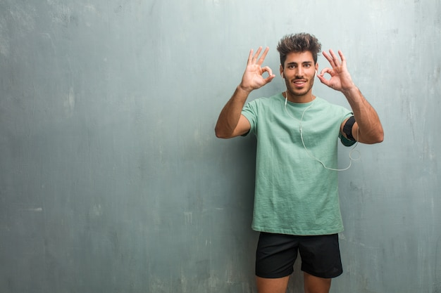 Young fitness man against a grunge wall cheerful and confident doing ok gesture