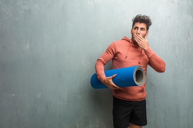 Young fitness man against a grunge wall covering mouth, symbol of silence and repression