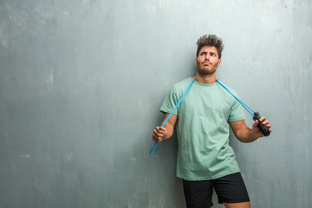 Young fitness man against a grunge wall crazy and desperate, screaming out of control, funny lunatic expressing freedom and wild. holding a jump rope.