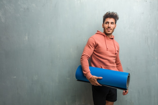 Young fitness man against a grunge wall crossing his arms, smiling and happy, being confident and friendly.