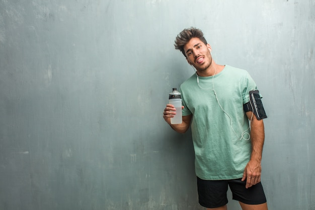 Young fitness man against a grunge wall expression of confidence and emotion, fun and friendly, showing tongue as a sign of play or fun. wearing an armband with phone.