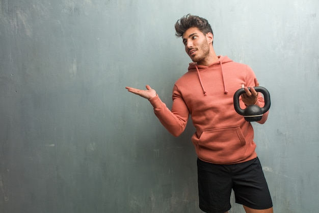 Young fitness man against a grunge wall holding something with hands, showing a product, smiling and cheerful, offering an imaginary object. holding an iron dumbbell.