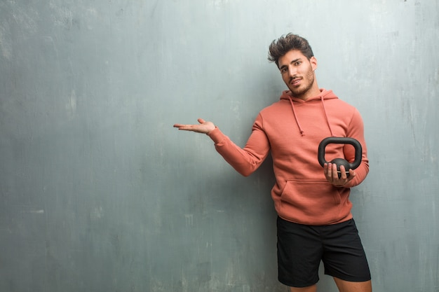 Young fitness man against a grunge wall holding something with hands, showing a product