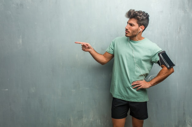 Young fitness man against a grunge wall pointing to the side, smiling surprised presenting something