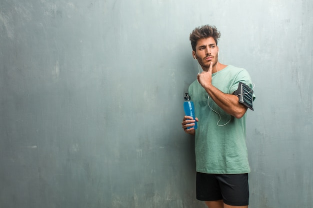 Young fitness man against a grunge wall thinking and looking up