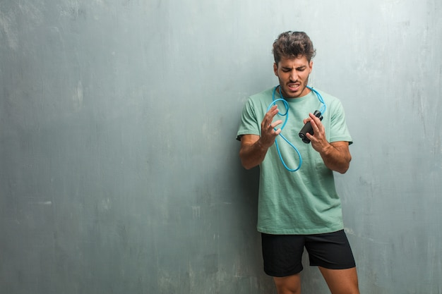 Young fitness man against a grunge wall very angry and upset, very tense, screaming furious, negative and crazy. holding a jump rope.