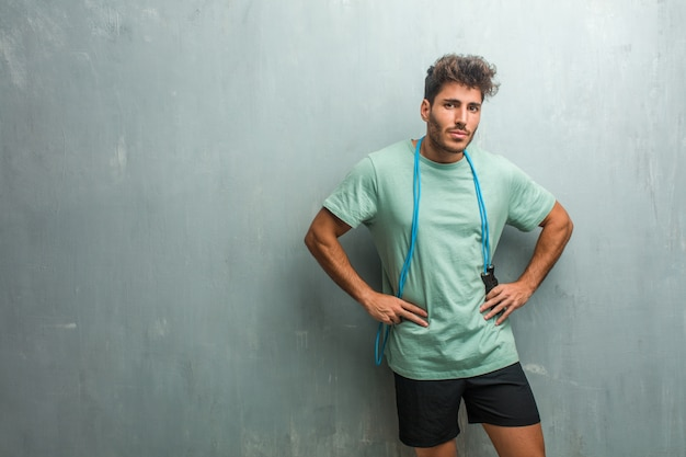 Young fitness man against a grunge wall very angry and upset, very tense