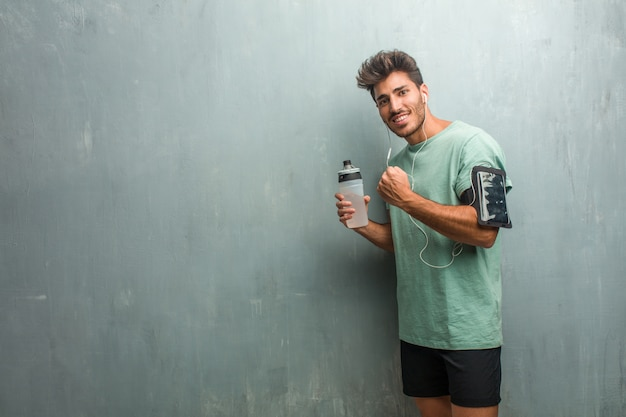 Young fitness man against a grunge wall very happy and excited, raising arms, celebrating a victory or success, winning the lottery. wearing an armband with phone.