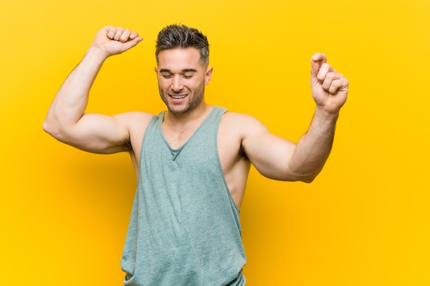 Young fitness man against a yellow background celebrating a special day, jumps and raise arms with energy.