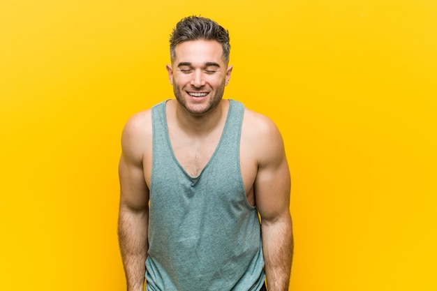 Young fitness man against a yellow background laughs and closes eyes, feels relaxed and happy.