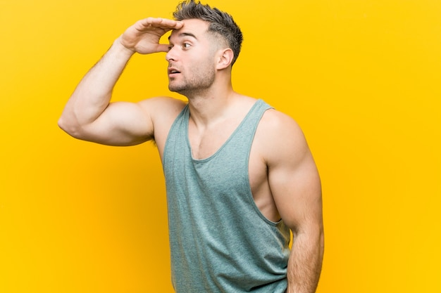 Young fitness man against a yellow background looking far away keeping hand on forehead.