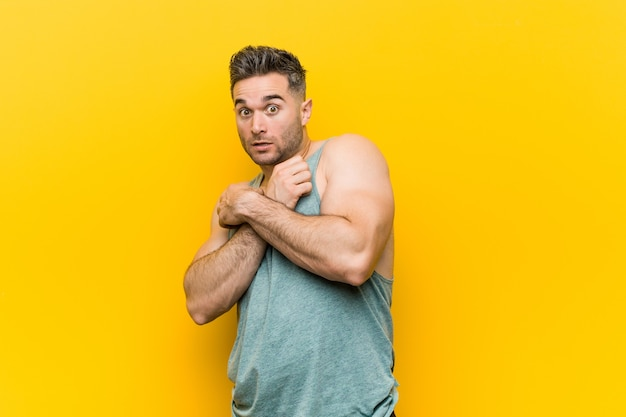 Young fitness man against a yellow background scared and afraid.