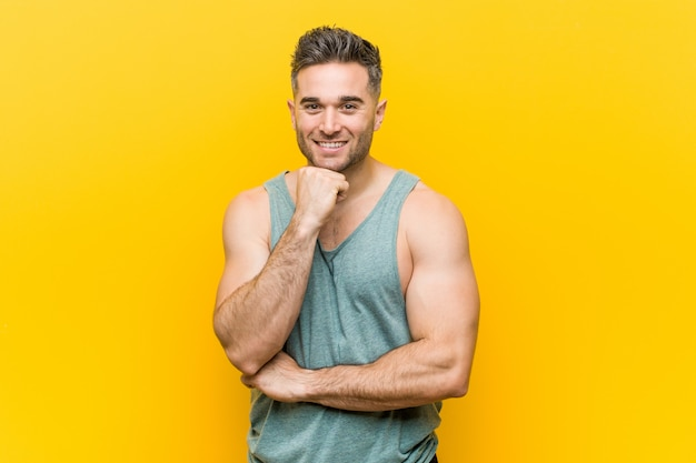 Young fitness man against a yellow background smiling happy and confident, touching chin with hand.