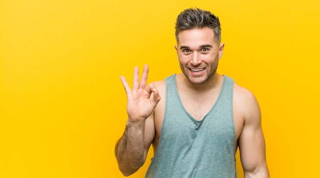 Young fitness man against a yellow background winks an eye and holds an okay gesture with hand.
