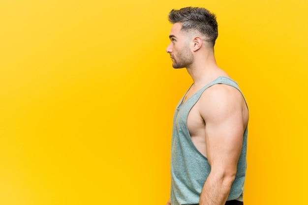 Young fitness man against a yellow gazing left, sideways pose.