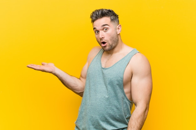 Young fitness man against a yellow impressed holding copy space on palm.