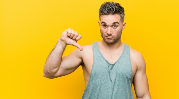 Young fitness man against a yellow wall showing a dislike gesture, thumbs down. disagreement concept.