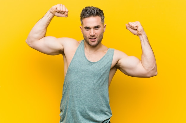 Young fitness man against a yellow wall showing strength gesture with arms, symbol of feminine power