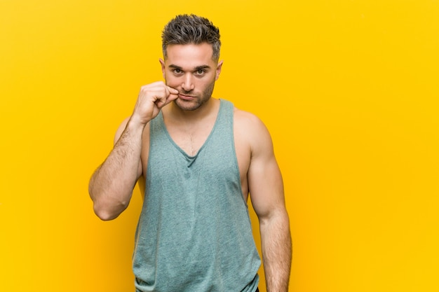 Young fitness man against a yellow  with fingers on lips keeping a secret.