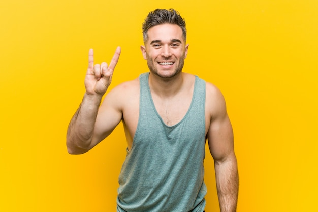 Young fitness man againstyellow  showing a horns gesture as a revolution .