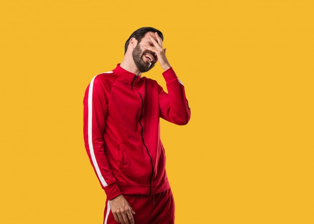 Young fitness man embarrassed and laughing at the same time