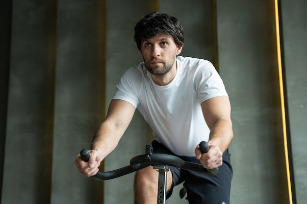 Young fitness man exercising his legs cardio training on bicycle in gym man working out on spinning bikes in gym
