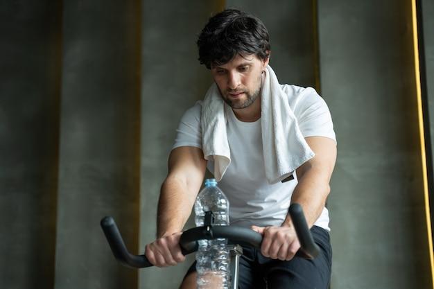 Молодой фитнес-человек, тренирующий свои ноги кардио-тренировку на велосипеде в тренажерном зале, человек, тренирующийся на спиннингах в тренажерном зале