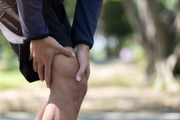Young fitness man holding his sports leg injury, muscle painful during training