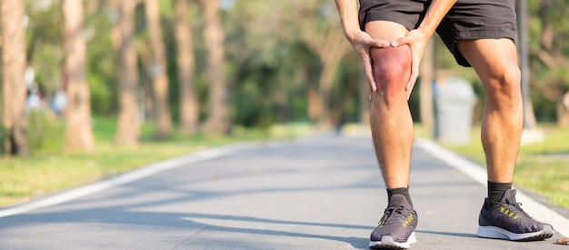 Young fitness man holding his sports leg injury. muscle painful during training