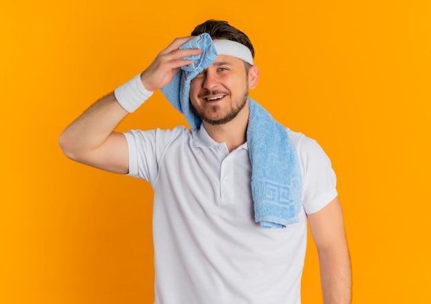 머리띠와 수건으로 흰 셔츠에 젊은 피트니스 남자가 카메라를보고 피곤하고 오렌지 배경 위에 서 웃고 들고