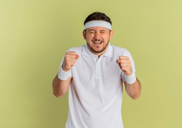 머리띠 떨림 주먹으로 흰 셔츠에 젊은 피트니스 남자가 올리브 배경 위에 서있는 그의 성공을 기쁘게 기쁘게 생각합니다.