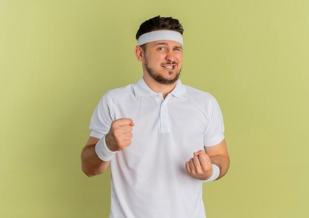 Молодой фитнес-мужчина в белой рубашке с повязкой на голову, сжимая кулаки, выглядит смущенным, стоя у оливковой стены