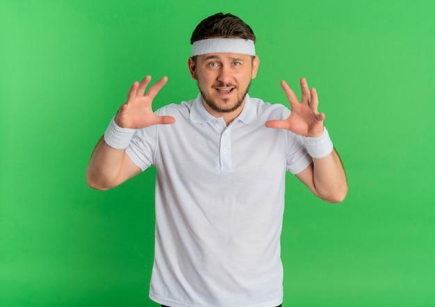 緑の背景の上に立って笑って、猫のように爪のジェスチャーをしているヘッドバンドと白いシャツの若いフィットネス男