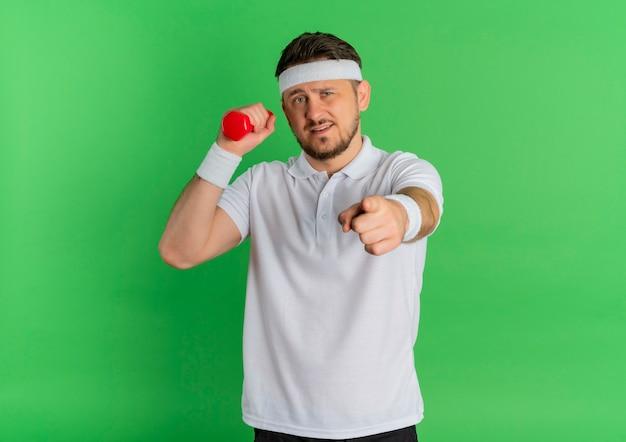 녹색 배경 위에 서있는 카메라를 손가락으로 가리키는 아령으로 운동을하는 머리띠와 흰 셔츠에 젊은 피트니스 남자