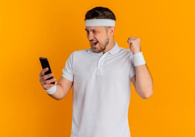 Молодой фитнес-мужчина в белой рубашке с оголовьем, держащий смартфон, сжимая кулак, счастлив и взволнован, стоя на оранжевом фоне