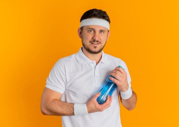 오렌지 배경 위에 서있는 얼굴에 미소로 카메라를보고 물 한 병을 들고 머리띠와 흰 셔츠에 젊은 피트 니스 남자