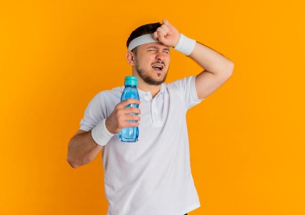 오렌지 배경 위에 서있는 운동 후 피곤하고 지쳐 보이는 물 한 병을 들고 머리띠와 흰 셔츠에 젊은 피트니스 남자
