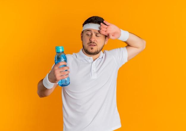 오렌지 배경 위에 피곤하고 지친 찾고 물 한 병을 들고 머리띠와 흰 셔츠에 젊은 피트니스 남자