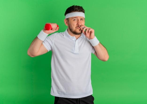 エクササイズをし、タバコを吸うダンベルを保持しているヘッドバンド、緑の背景の上に立っている悪い習慣のスポーツコンセプトを持つ白いシャツの若いフィットネス男